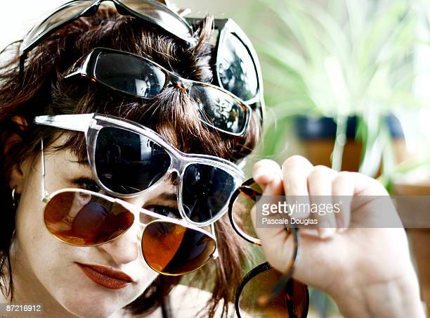 several pairs of sunglasses on one head - excess stock pictures, royalty-free photos & images