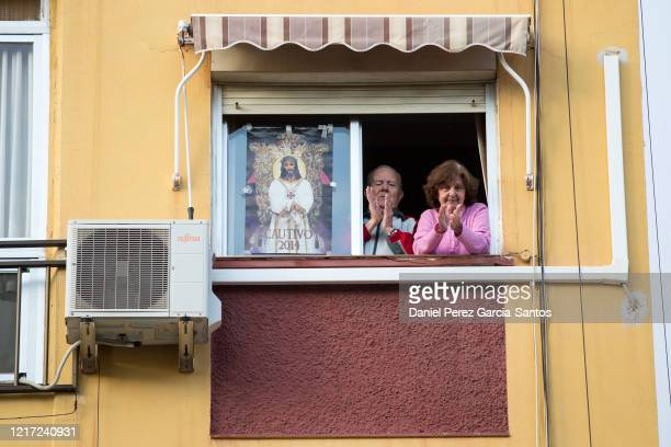 Several people applaud during a tribute to front-line healthcare workers along with an image of Cristo Cautivo during Holy Week while the world...