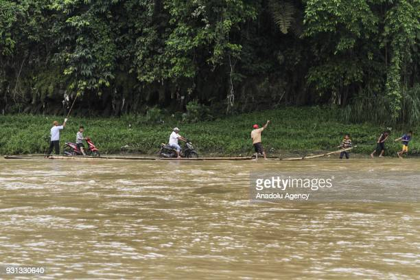 Several people assist motorcyclists to pull up their vehicles onto wooden raft to cross Cisadane River in Rumpin Bogor West Java Indonesia on March...