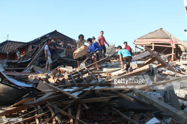 Several people evacuate one of victims trapped between collapsed buildings following an earthquake at Bangsal village in North Lombok West Nusa...