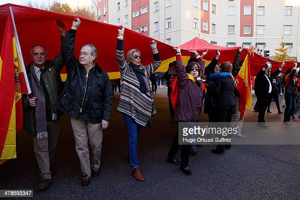 Several people hold a giant flag of Spain during the protest to demand justice for victims of terrorism in Madrid Strasbourg's ruling is allowing the...