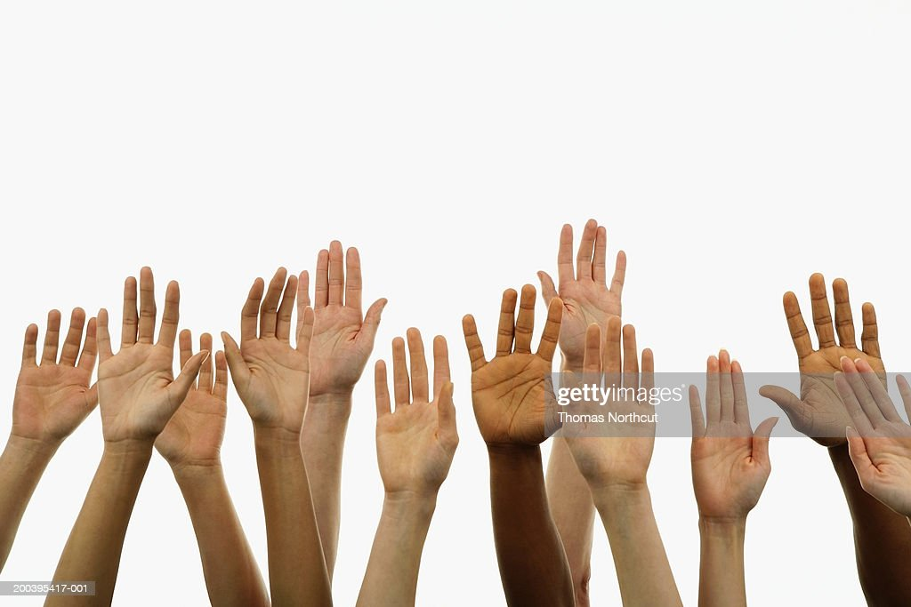 Several people holding their hands in the air : Stock Photo