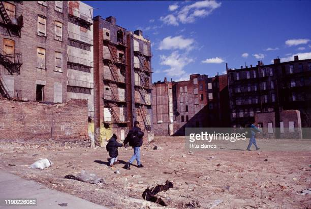 Several people including a woman and a child walk across a vacant lot surrounded by abandoned and boarded up buildings Harlem New York New York 1997