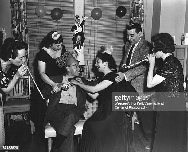 Several people including writer and artist Mel Harris at a party with noisemakers balloons and party hats New York ca1950s Photo by...