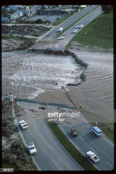 Several people observe a collapsed road February 21 1980 in California Several storms battered the California coast with rain wind mudslides and...