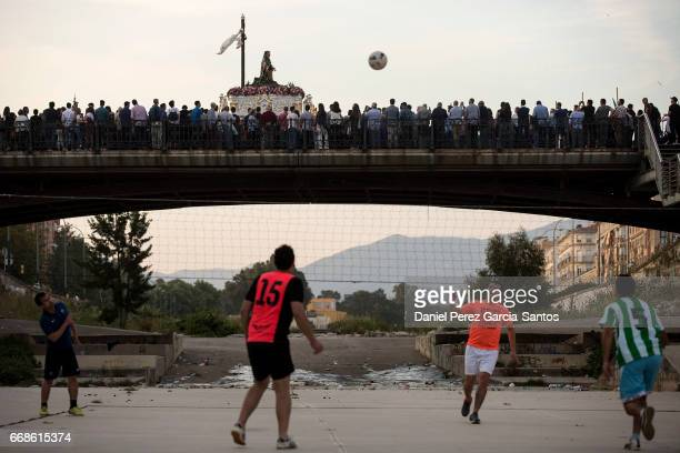 Several people play a soccer volleyball game during the procession of the Santo Traslado brotherhood during Holy Week on April 14 2017 in Malaga...