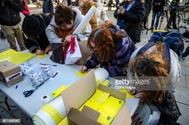 Several people seen writing a desire for freedom in a yellow tag to hang on the tree of wishes Òmnium Cultural one of the main Catalan...