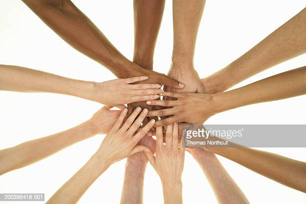 Several people stacking hands on top of each other, overhead view