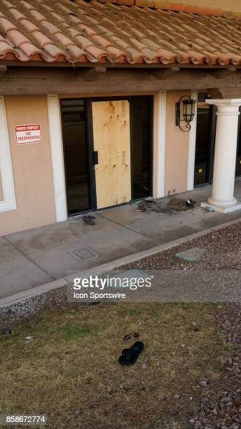 Several personal items sun glasses and a lone flip flop sit in front of a boarded glass door after it was broke by people escaping the gunfire at...