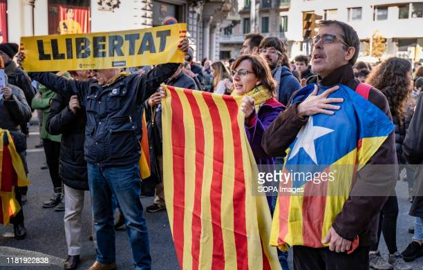 Several protesters hold flags for the independence of Catalonia during the demonstration. About 150 people have gathered in front of the consulate...