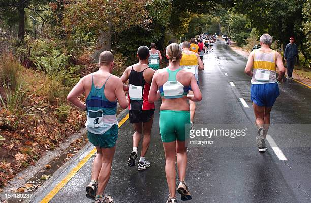 Several runners on a marathon running on a paved road