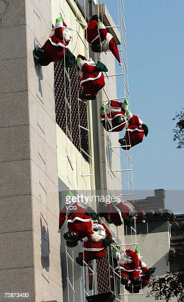 Several Santa Claus decorations hang on the wall to mark upcoming Christmas on December 22 2006 in Yangzhou China While Christmas Day is not a public...