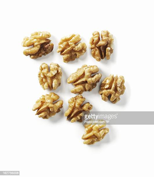 Several shelled walnuts on white background