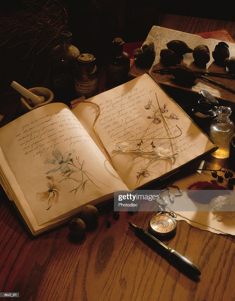 Several small items from a journal with sketches to herbs lay on a wood table : Foto de stock
