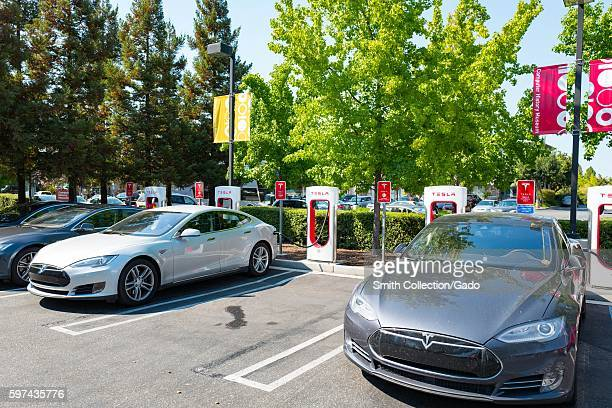 Several Tesla automobiles plugged in and charging at a Supercharger rapid battery charging station for the electric vehicle company Tesla Motors in...
