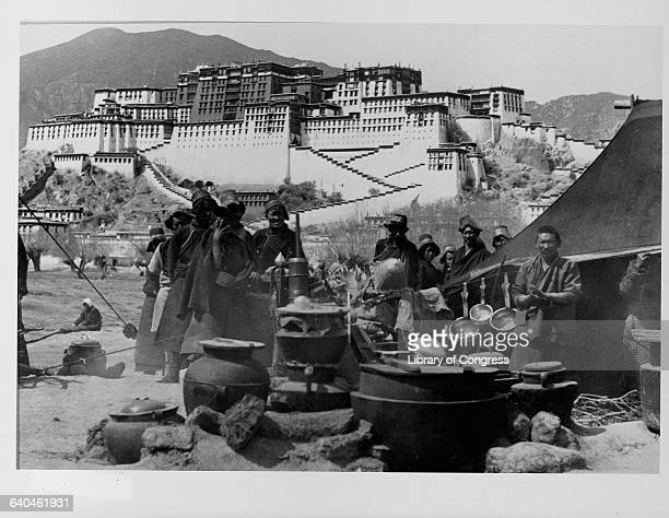 Several Tibetans stand by a tent with the Potala the palace of the Dalai Lama behind them