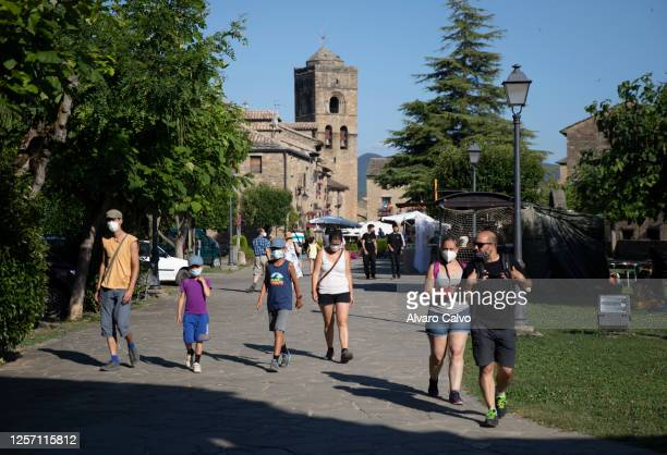 Several tourists walk through the town of Ainsa on July 19 2020 in Ainsa Spain The use of masks is mandatory throughout the community of Aragon to...