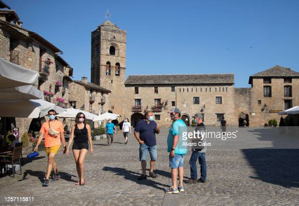 Several tourists with masks walk through the town of Ainsa on July 19 2020 in Ainsa Spain The use of masks is mandatory throughout the community of...