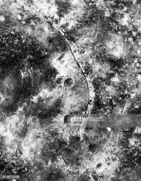 Several trucks belonging to communist forces lay overturned on a rural road part of the Ho Chi Minh Trail after the US Air Force bombed the road in...