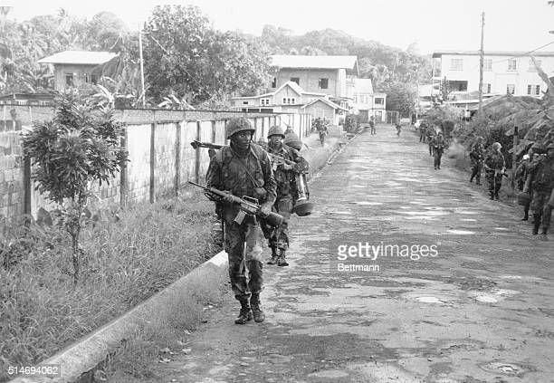Several United States Marines carry their weapons and equipment on a road in Greenville shortly after landing in the 1983 Invasion of Grenada