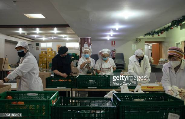 Several volunteers prepare tuppers with food in the soup kitchen of the parish of El Carmen on Christmas Day on December 25, 2020 in Zaragoza, Spain....