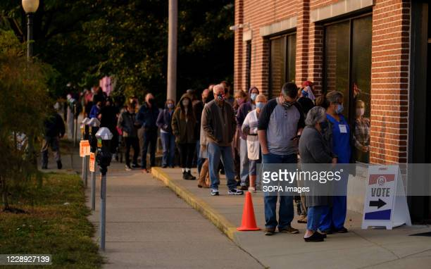 Several voters wearing masks are seen lined up outside Election Central during the first day of early voting in Monroe County, Indiana. Over 100...