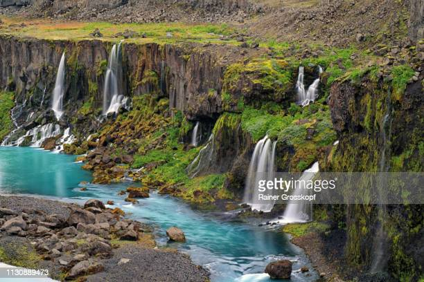 Several waterfalls flowing into a river in a canyon in a remote area
