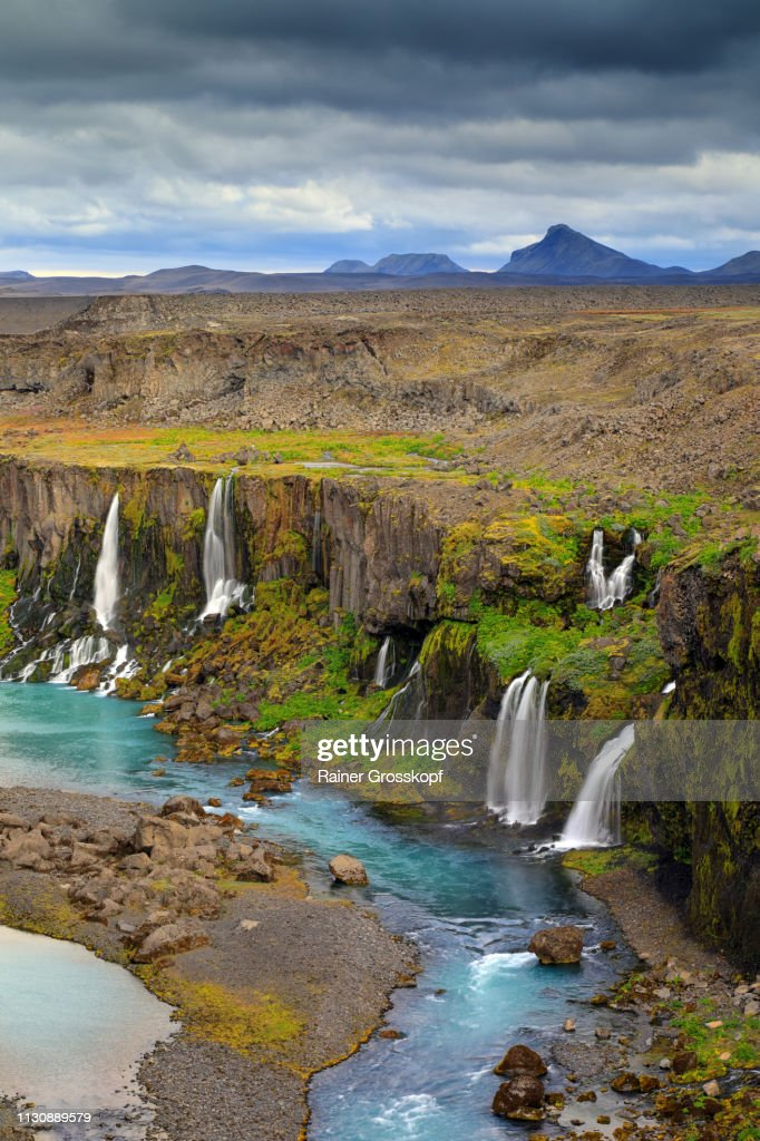 Several waterfalls flowing into a river in a canyon in a remote area : Stock-Foto