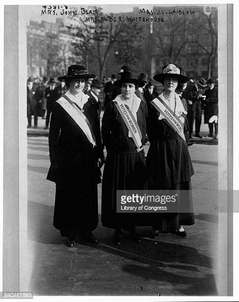 Several women wear sashes reading Votes for Women in a suffrage parade along a city street USA