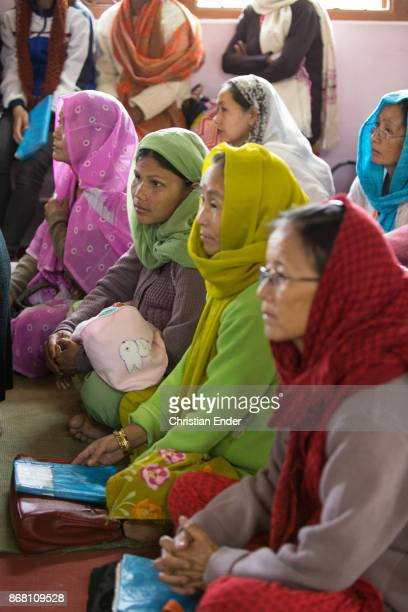 Several women wearing a sari are sitting on the floor inside a church in Kalimpong