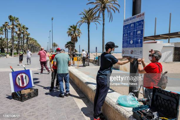 Several workers are working on the Malvarrosa beach in the installation of the informative poster on the occasion of the entry into Phase 2 of the...