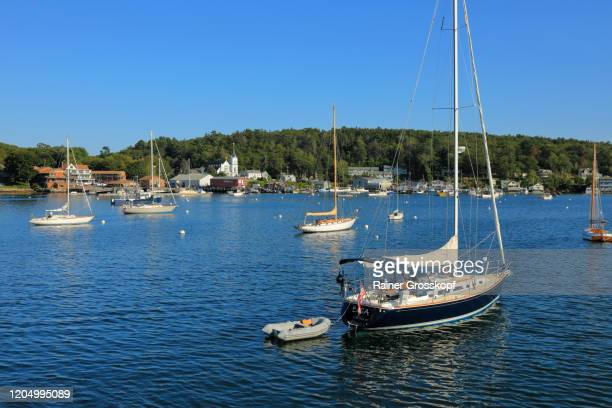 several yachts in the bay of a small town with a white church - rainer grosskopf stock-fotos und bilder