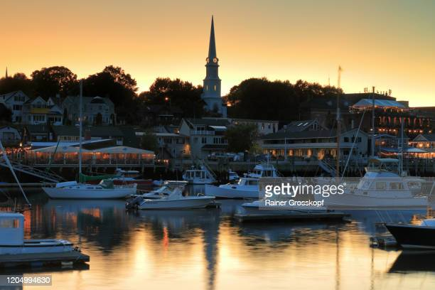 several yachts in the harbor of camden with illuminated houses and a church at sunset - rainer grosskopf foto e immagini stock