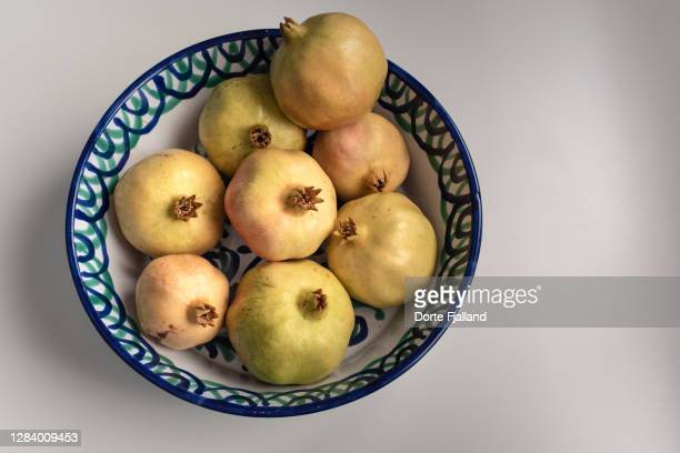 several yellow skinned pomegranates in a ceramic bowl - dorte fjalland fotografías e imágenes de stock