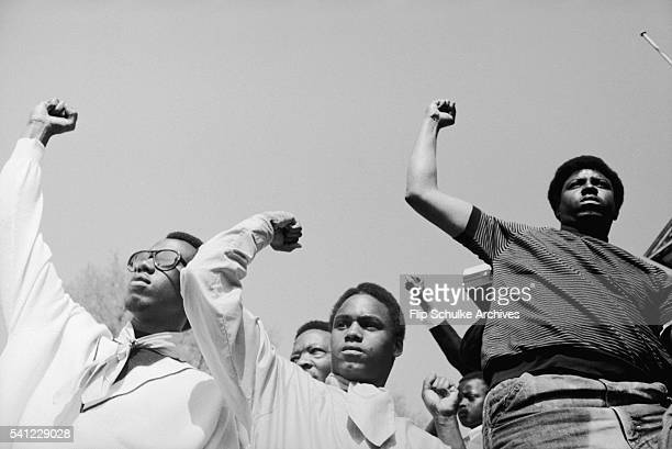 Several young men raise their fists in the black power salute at a civil rights rally