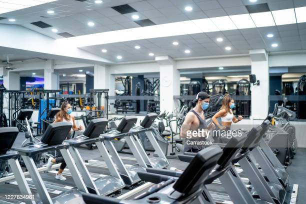 several young people running on treadmill in gym wearing face mask. - face guard sport stock pictures, royalty-free photos & images