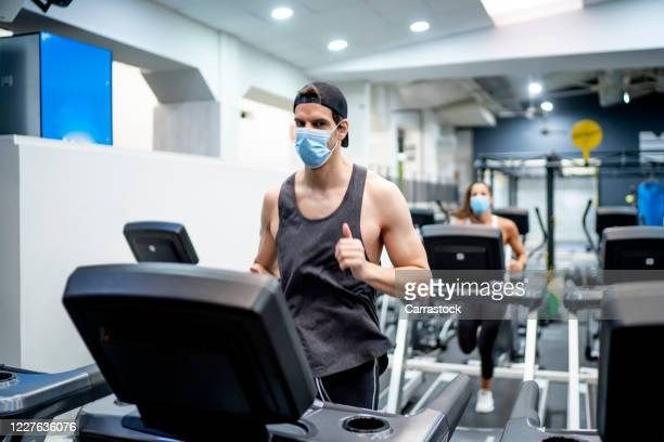 several young people running on treadmill in gym wearing face mask. - palestra club ginnico foto e immagini stock