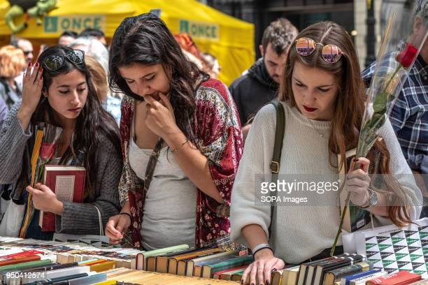 Several young women are seen looking at books in the stalls of the Ramblas Catalunya celebrates the 'Day of Sant Jordi' the day of books and roses...