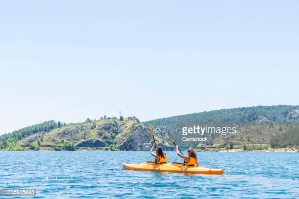 several young women canoeing kayaking on lake. - castilla la mancha fotografías e imágenes de stock