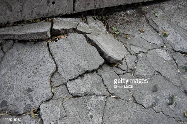 severely cracked and lifted concrete footpath - earthquake stock pictures, royalty-free photos & images