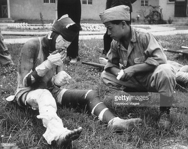 A severely wounded Korean soldier smoking a cigarette in the grounds of an advance casualty cleaning unit Original Publication Picture Post 5086 We...