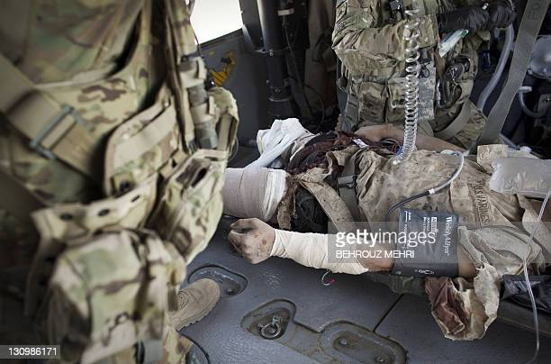A severely wounded US Marine hit by an Improvised Explosive Device receives medical treatment from US Flight Medic sergeant Megan Ford and Crew Chief...