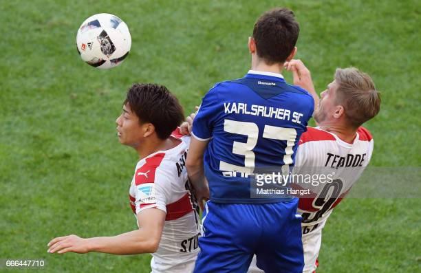 Severin Buchta of Karlsruhe jumps for a header with Takuma Asano and Simon Terodde of Stuttgart during the Second Bundesliga match between VfB...