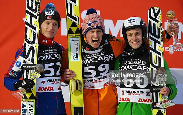 Severin Freund of Germany celebrates at the podium next to Rune Velta of Norway and Roman Koudelka of Czech Republic after winning the FIS Ski...