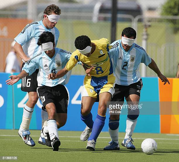 Severino Silva of Brazil gets tackled by Lucas Rodriguez and Oscar Moreno of Argentina in the Football 5aside B1 Gold Medal match between Brazil and...