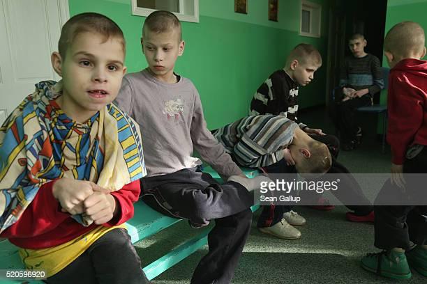 Severlyhandicapped boys sit on a bench in their wing at the Vesnova Home for Invalid Children on April 3 2016 in Vesnova village near Glusk Belarus...