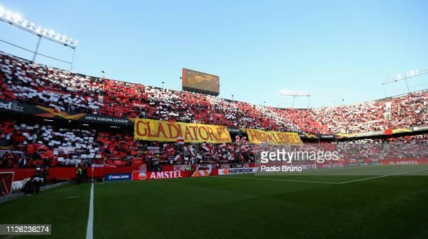 Sevilla fans hold flags during the UEFA Europa League Round of 32 Second Leg match between Sevilla v SS Lazio at Estadio Ramon Sanchez Pizjuan on...