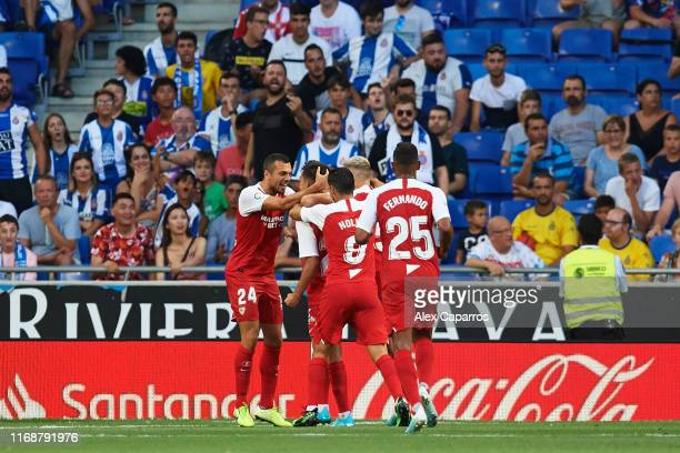 Sevilla FC players celebrate with their teammate Sergio Reguilon after scoring the opening goal during the Liga match between RCD Espanyol and...