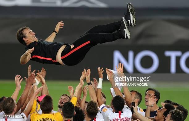 Sevilla players throw Sevilla's Spanish coach Julen Lopetegui in the air after the UEFA Europa League final football match Sevilla v Inter Milan on...