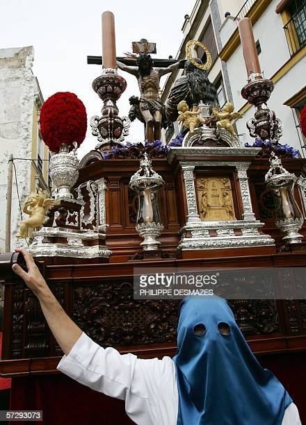 """Penitent walks in the brotherhood parade during the procession """"Nuestra Senora de la Hiniesta"""" for the first day of the famous holy week in Seville,..."""